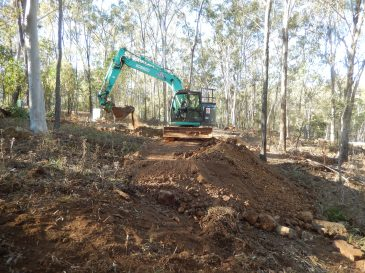 Excavator creating terraced roadway