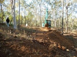 Excavator forming roadway terrace