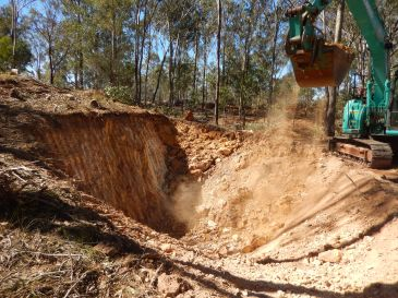 Excavator digging trench on contour