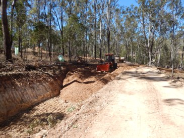 Loader spreading woodchip into holes