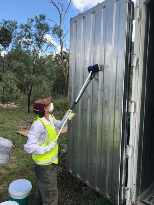 mopping down the doors of the container