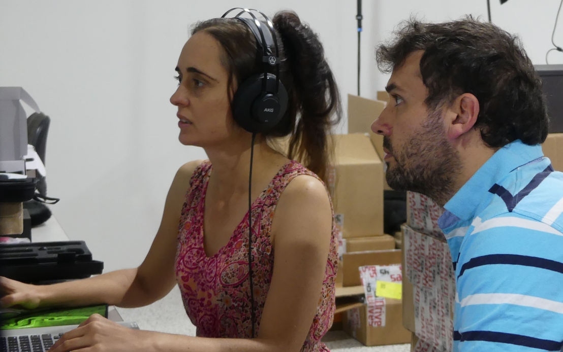 Mary gives instructions on audio editing to a volunteer