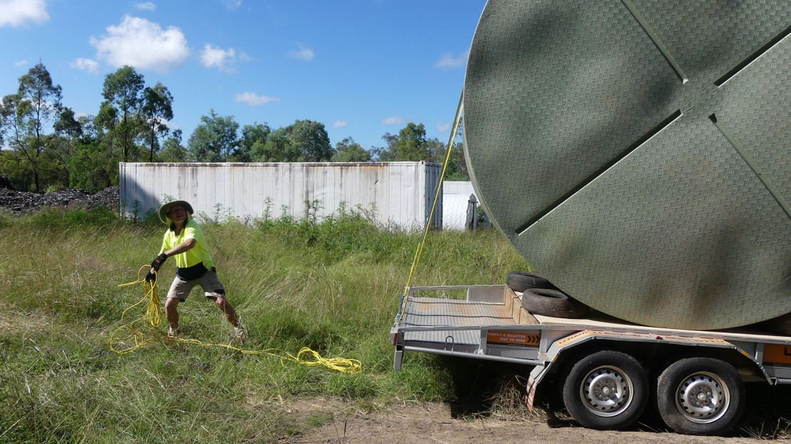 A volunteer throws straps over the tank to secure it for transportation