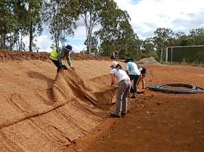 Volunteers spread the coconut fibre mat