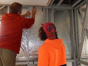Corny instructing Nicky how to insert insulation into the walls of the caretaker's residence