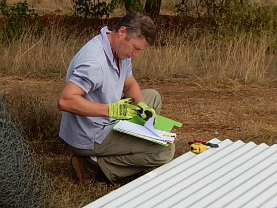 Corny cutting corrugated sheets which will be used to clad the caretaker's house