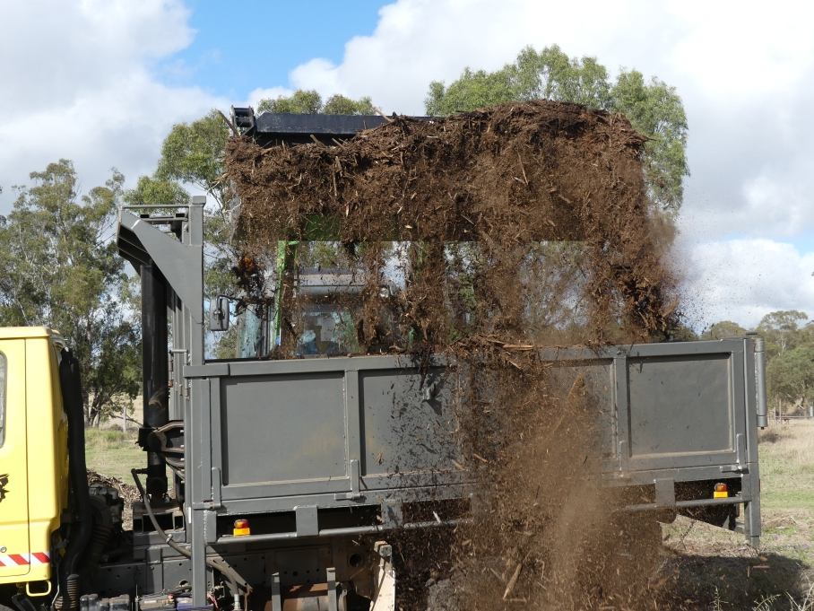 Tractor loads woodchip into Tip Truck