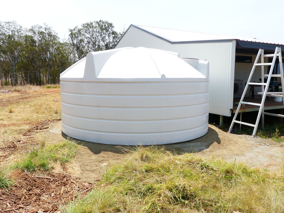 New water tank in place on its pad next to the house