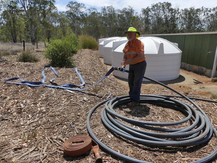 Wayne prepares long hoses between the dam and garden bed
