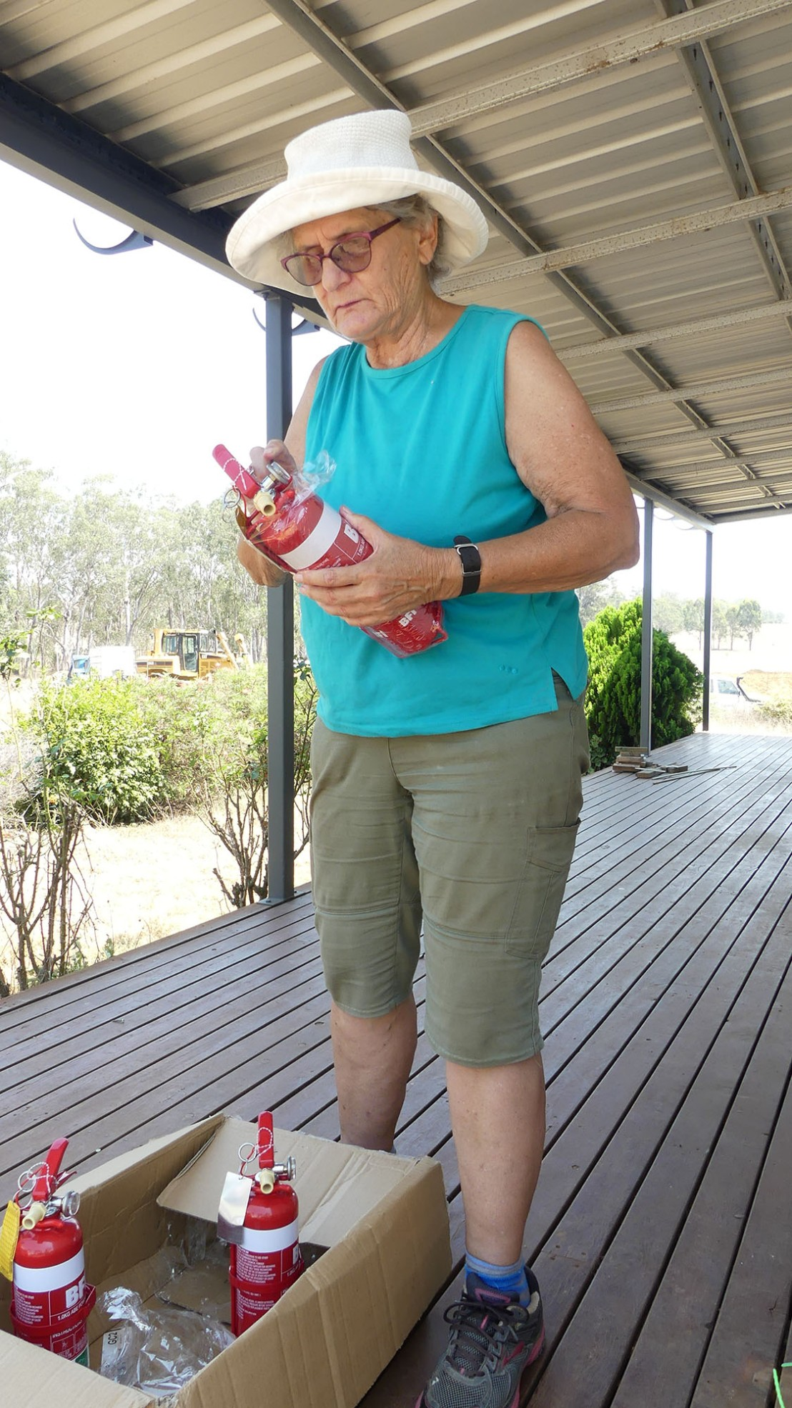 Catherine prepares new fire extinguishers for installation