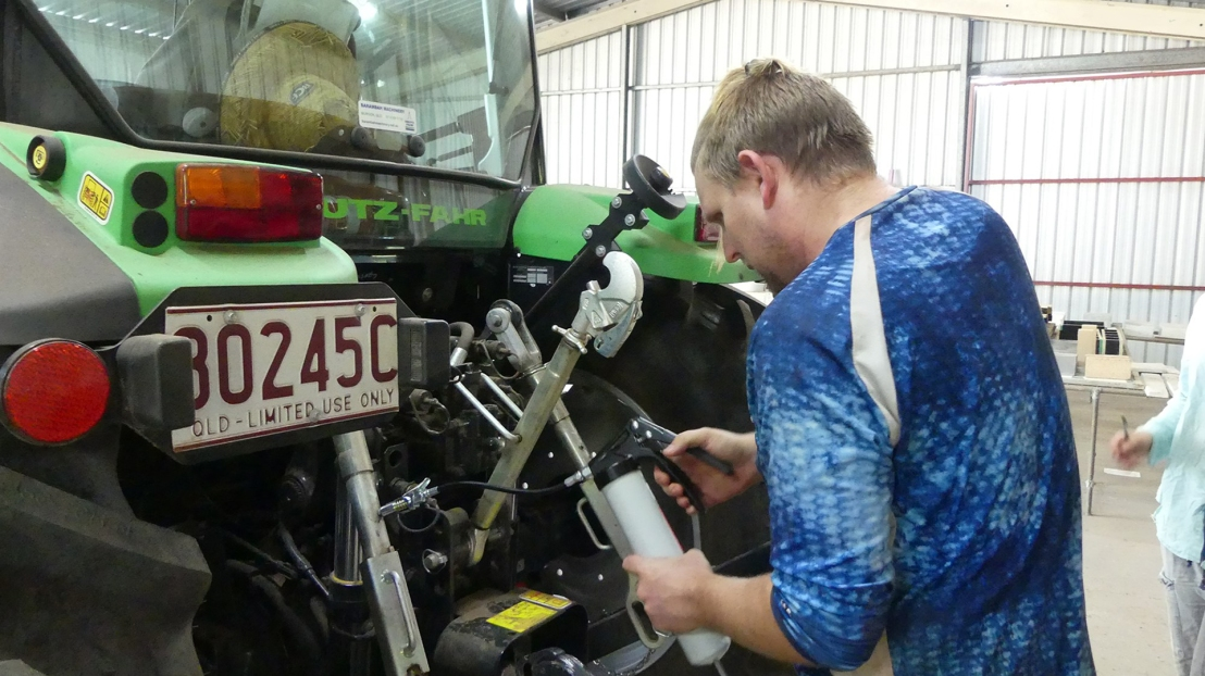 Tractor maintenance training, grease application, April 2020.
