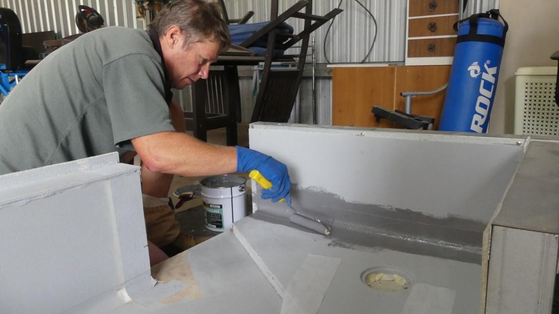 Volunteer applies waterproofing membrane coating, April 2020.