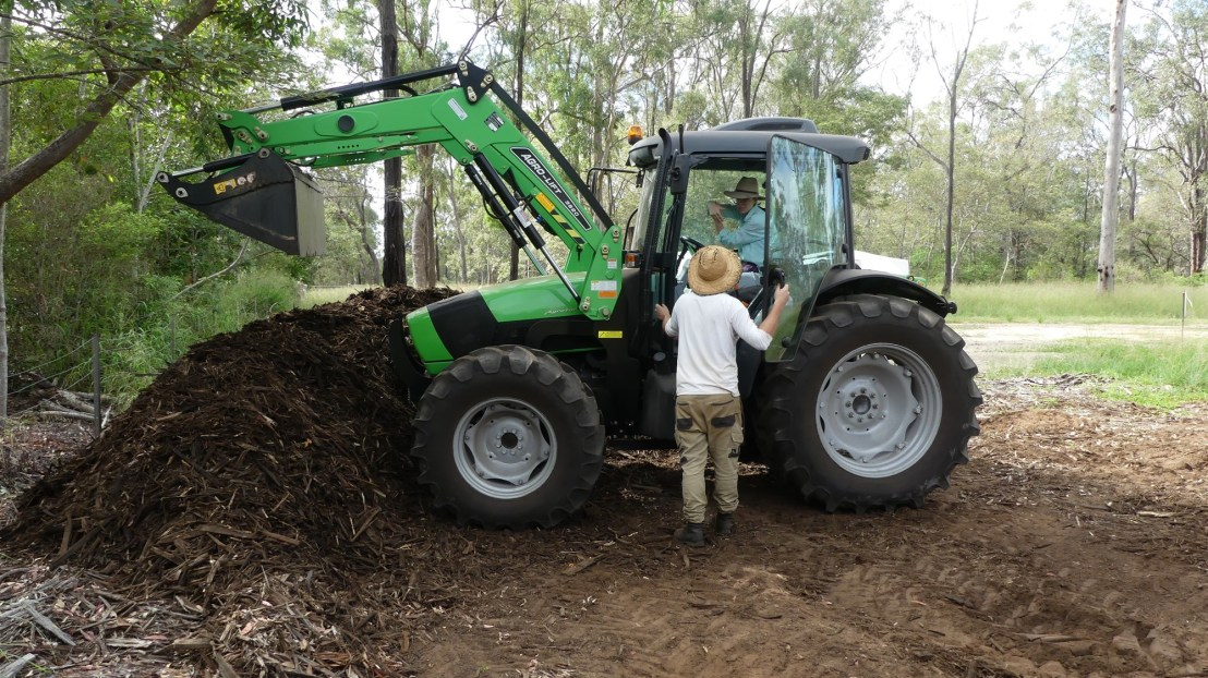 Tristan instructs volunteer to efficiently move mulch, April 2020.