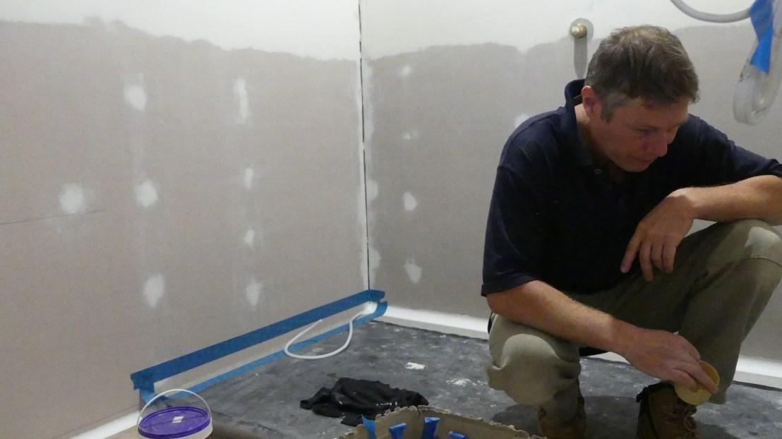 Volunteer prepares shower area to be waterproofed, May 2020.