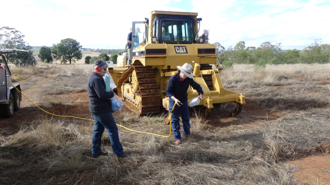 Volunteers learn to maintain the dozer, July 2020.