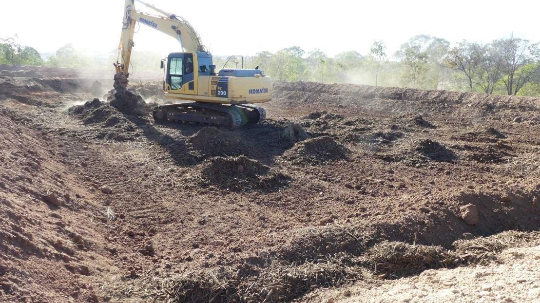 Excavator spreads mulch in base of terrace, August 2020.